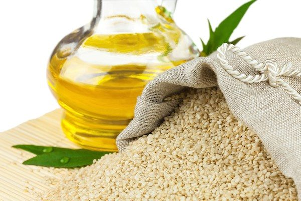 Macro view of sesame seeds in flax sack and glass bottle of sesame oil on mat isolated on white background